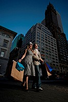 Low angle view of a young couple walking on the road, New York City, New York, USA