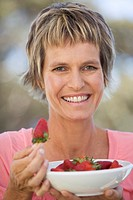 A woman eating a bowl of strawberries