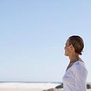 A mature woman standing on a beach