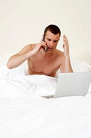 Young man in bed, working on laptop
