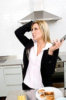 Businesswoman having breakfast in the kitchen and talking on the phone