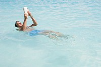 Man reading a book while floating in ocean