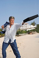 Businessman tossing his briefcase out to sea