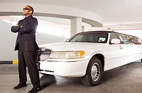 A chauffer standing by a stretch limousine