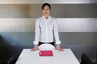 Businesswoman standing at head of conference table