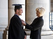 A mother checking her graduate son´s gown