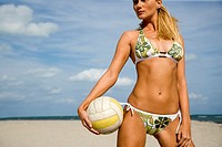 A young woman on a beach holding a ball