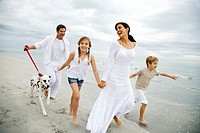 A family walking the dog on a beach