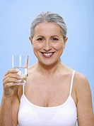 Senior woman holding glass of water, portrait