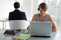 Business woman with headset working on laptop, male colleague in background