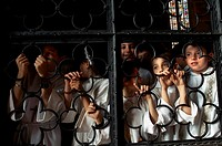 Group of children looking through a window of a church, Orvieto, Umbria, Italy