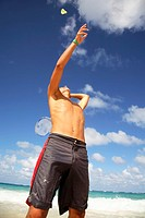 Young man playing batminton on beach
