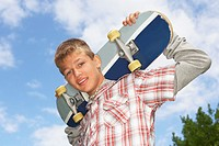 A teenage boy holding a skateboard