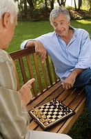 Two elderly men playing chess
