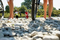 Friends walking on pebbles with their cycles