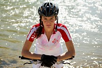 A woman sitting on her cycle, river in background