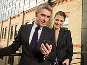 Two businesspeople checking a mobilephone