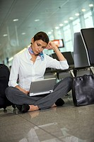 A businesswoman using her laptop in the airport