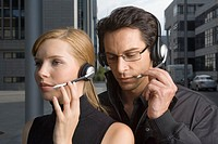 Two business people wearing headsets
