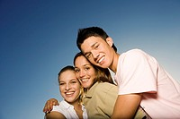 Three teenage friends hugging