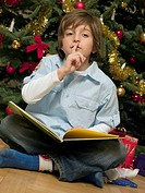 A boy reading a book in front of the Christmas tree
