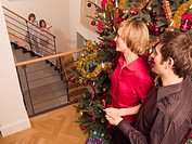 Children looking at their parents from the stairs