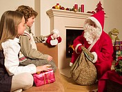 Man dressed as Santa giving gifts to children
