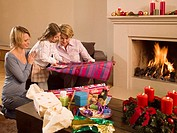 Girl helping her mother and grandmother wrap Christmas presents
