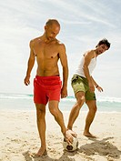 Men playing football on the beach