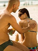 Man applying suntan lotion on his girlfriend