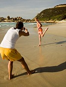 Man taking pictures of his girlfriend on the beach