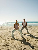 A couple performing yoga on a beach