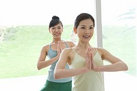 Young women doing yoga exercise, front view