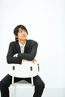 Young businessman sitting on chair, looking away, front view, white background, copy space