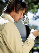 Man looking at his glass of white wine