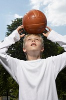A boy standing with a basketball on his head