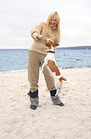 Young woman playing with a dog on the beach