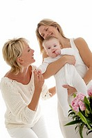 Mother holding baby, grandmother smiling