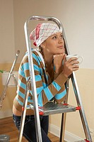 Close-up of a young woman leaning on a step ladder and thinking