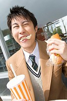 Teenage boy eating bread and holding disposable cup at terrace