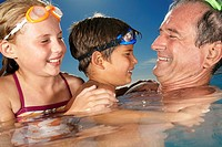 Kids Wearing Swim Goggles in Pool with Grandfather