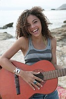 Portrait of a young woman playing the guitar and smiling on the beach