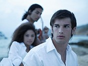 Close-up of a young man on the beach with his friends in the background