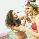 Close-up of a young woman adjusting a snorkel on a young woman