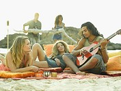 Young man playing the guitar with two young women lying beside him