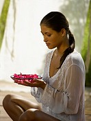 A young woman holding a bowl of rose petals