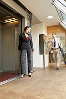 Businessman walking and talking to a businesswoman (thumbnail)