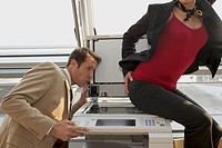 Businesswoman sitting on a photocopy machine and a businessman looking at her