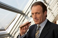 Close-up of a businessman holding a cigar