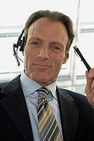 Close-up of a businessman wearing headset and holding a pen